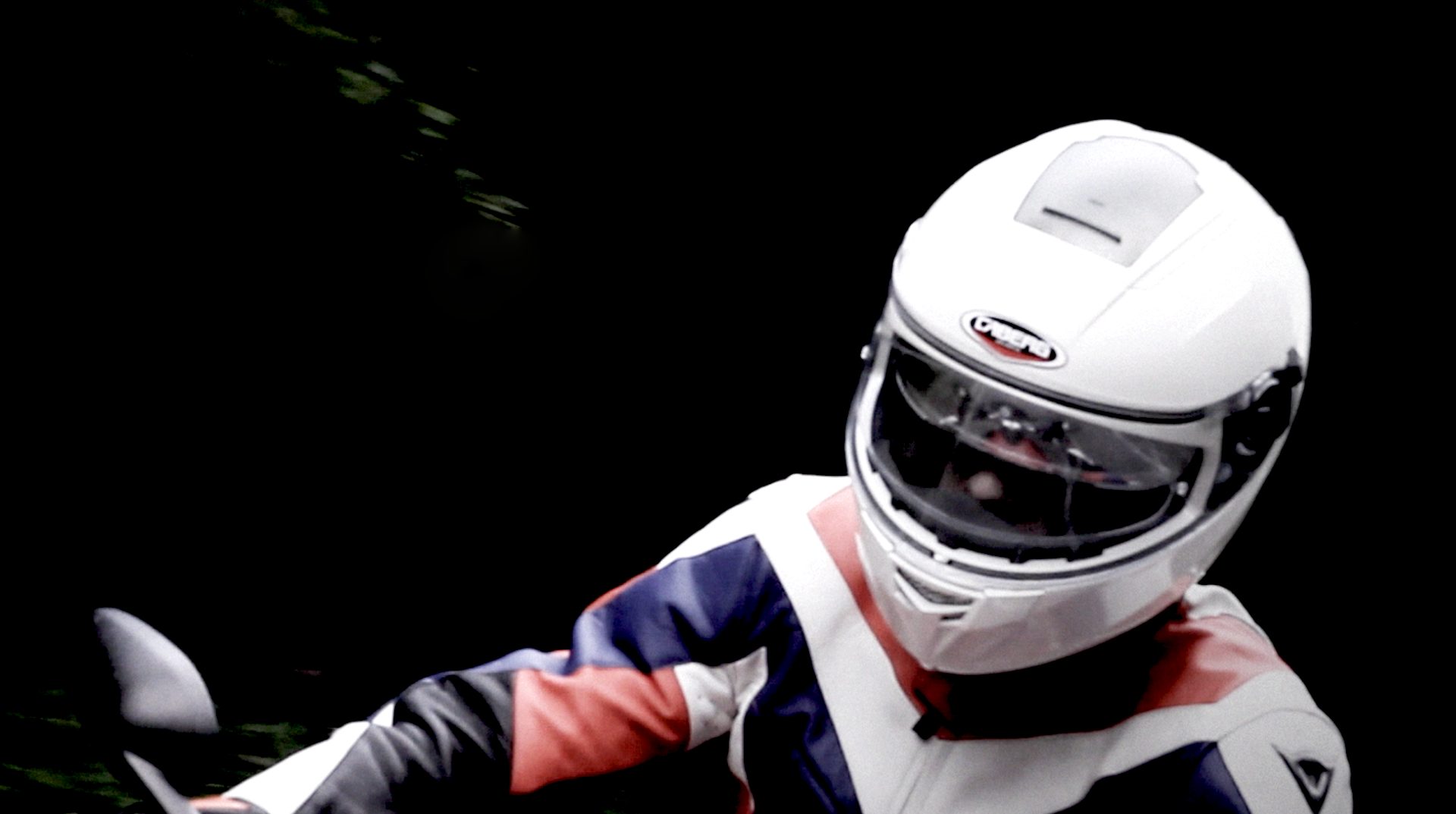 Medium shot of a motorbike rider wearing a white helmet and a leather jacket