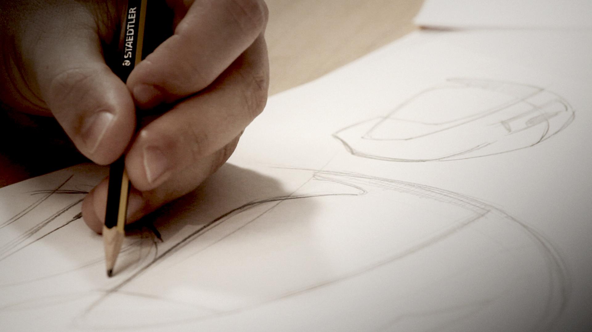 Hand drawing a motorbike helmet on paper