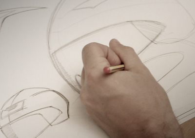 Hand drawing a motorbike helmet on paper